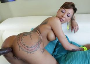 A slut that has hawt tattoos is riding a big darksome 10-Pounder on the sofa