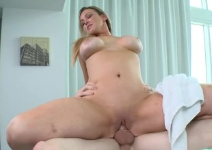 A blonde with a large rack is getting her pussy fucked at a porn spa