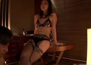 Japanese brunette in bra and stockings performs hot handjob