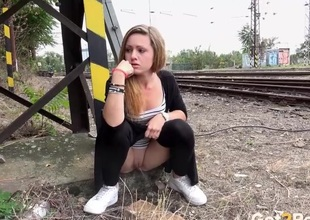 Girl takes a piss by the acquaint tracks
