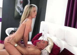 A blonde is with an old man with a big cock, sucking him off