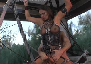 A redhead is with her blonde friend and a dude in a domination scene