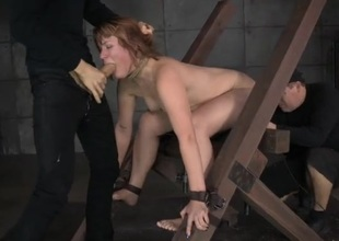 Cocks pound the redhead in nasty bondage