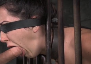 Manacled underling in a cage opens her mouth for face fucking