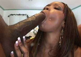 Buxom black chick in knee high boots worships two big cocks like a big gun