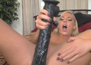 A blonde that's filled with lust is riding a big huge dildo