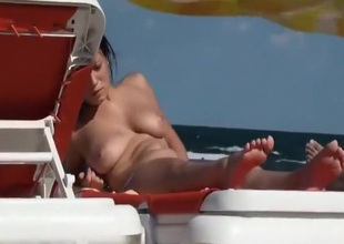 Sunbathing topless on a sunny swain