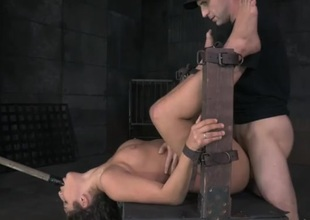 Babe in a bondage device takes a hard throb