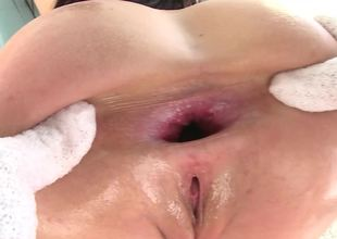 A brunette that loves anal is covered with oil and she is fucked