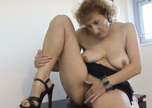 Stacked of age lady lies on the floor satisfying her desires with her skillful fingers