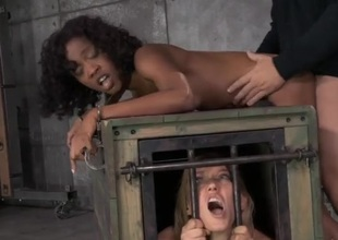 Girl in a cage watches a bound black damsel acquire fucked