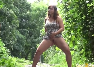 Chubby doll in a duds goes pee outdoors